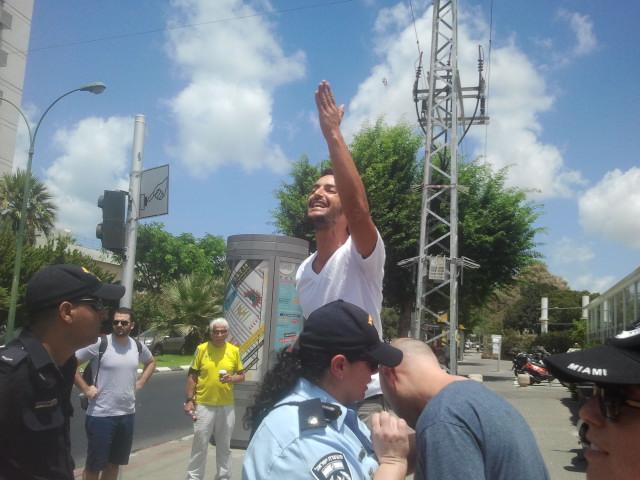אדם נעמד מול ההפגנה ומקלל