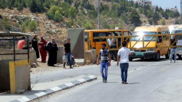 חסימה בכניסה למחנה הפליטים אל-פוואר: תושבים חוזרים הביתה עם קניות. צילום: נסר נוואג'עה, בצלם. (4.7.16)