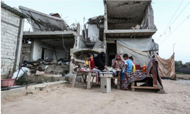 משפחה פלסטינית אוכלת ליד ביתה ההרוס ברצועת עזה. קרדיט: arab48.com