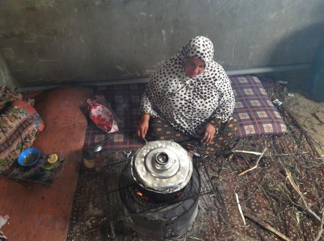 """אישה פלסטינית במחנה """"נהר אל-בארד"""" מבשלת על תנור עצים קטן. קרדיט: safa.ps"""