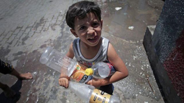 ילד פלסטיני הולך למלא מים בבקבוקים בשל משבר המים המתמשך. קרדיט: safa.ps
